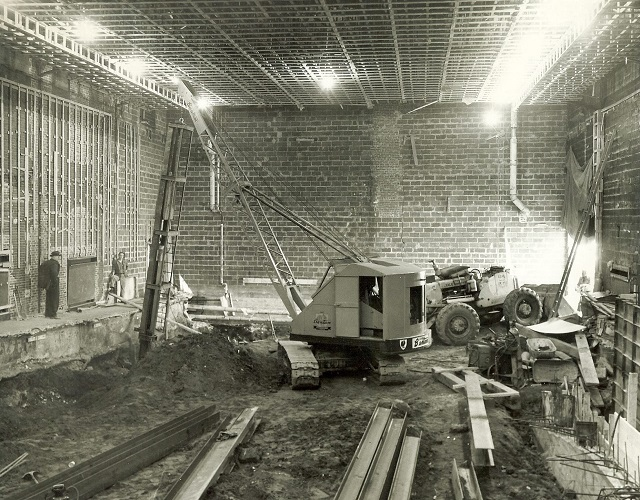 This picture is showing a crane driving pile inside the YMCA in Bath, ME - 1962